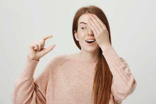 Garota ruiva engraçada e fofa cobrindo um olho e mostrando um pequeno objeto Foto gratuita