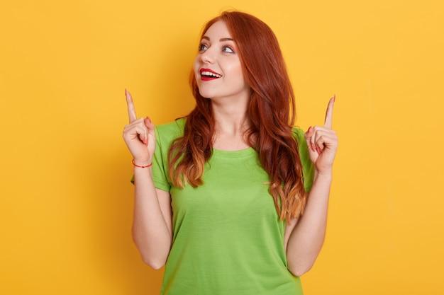 Garota ruiva feliz e surpresa em uma camiseta verde casual parecendo surpresa e apontando para cima com os indicadores, posando isolados Foto gratuita