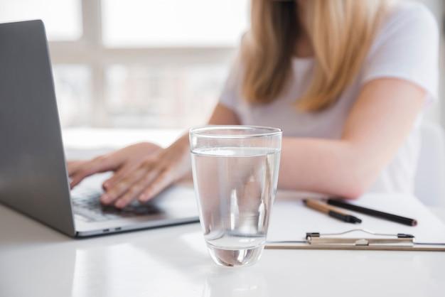 Garota saudável usando laptop com copo de água Foto gratuita