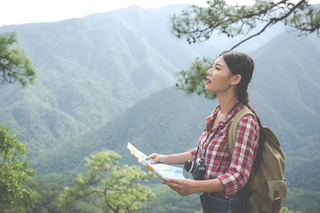 Garota se levantou para ver o mapa no topo da colina em uma floresta tropical junto com mochilas na floresta. aventura, caminhadas. Foto gratuita