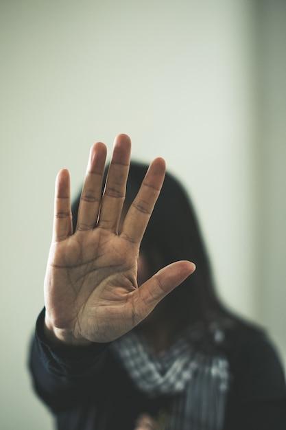 Garota sendo atingida. jovem com contusões no rosto mostrando sinal de stop Foto Premium