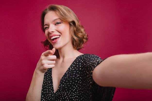 Garota sensual com tatuagem bonita no braço fazendo selfie mulher encaracolada de cabelos curtos em vestido preto tirando foto de si mesma na sala com interior roxo. Foto gratuita
