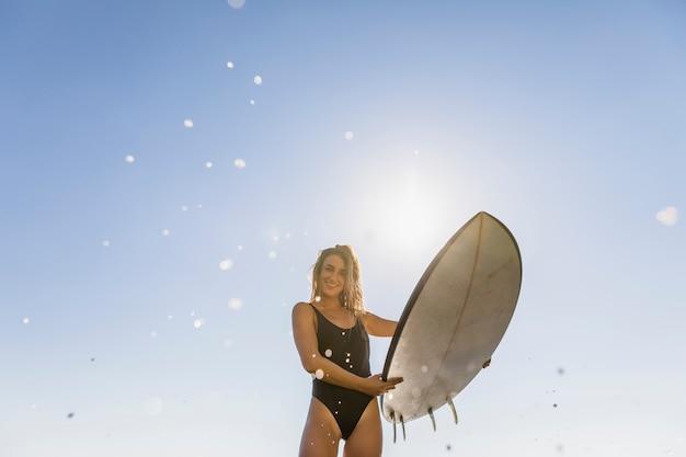 Garota sexy com prancha de surf na praia Foto gratuita
