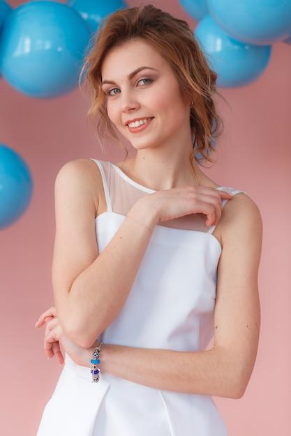 Garota sexy jovem sorrindo no retrato de vestido branco Foto gratuita