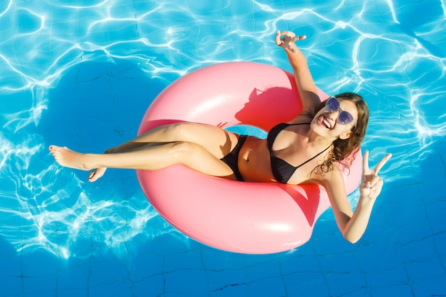 Garota sexy se divertindo e rindo em um anel-de-rosa inflável. mulher, em, piscina Foto Premium