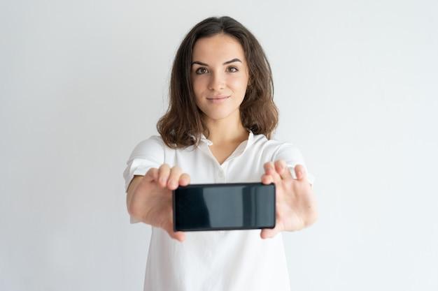 Garota simpática positiva apresentando novo serviço móvel ou app na tela do celular. Foto gratuita