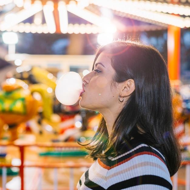 Garota soprando goma de mascar Foto gratuita