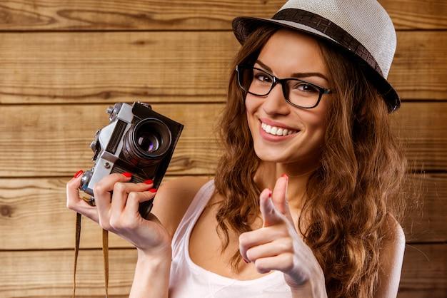 Garota sorri e faz uma foto em uma câmera antiga. Foto Premium