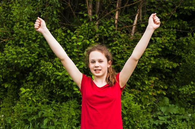Garota sorridente animada levantou as mãos em gesto de sucesso no parque Foto gratuita