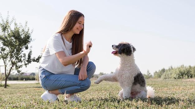 Garota sorridente com cachorro fofo Foto gratuita
