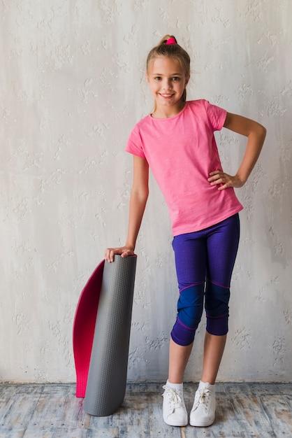 Garota sorridente confiante com a mão no quadril segurando rolando esteira de exercício Foto gratuita