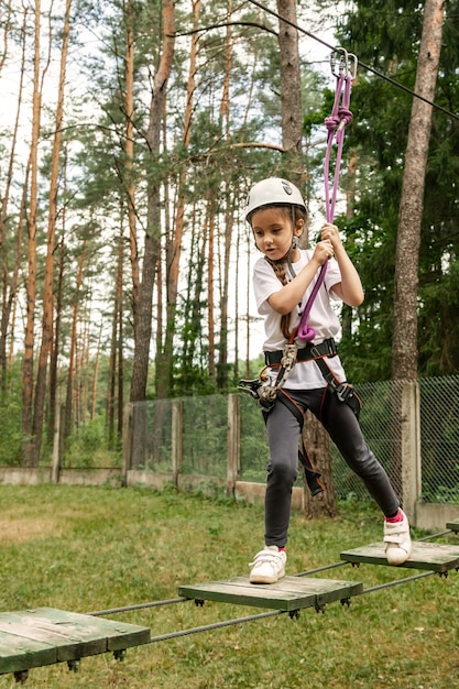 Garota subindo um caminho em uma corda de parque Foto Premium