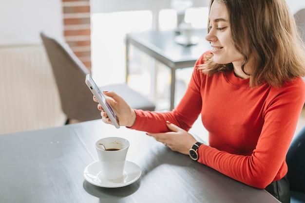 Garota tomando café em um restaurante Foto gratuita