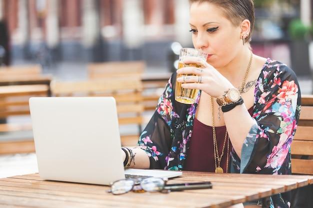 Garota trabalhando no computador dela e bebendo cerveja Foto Premium