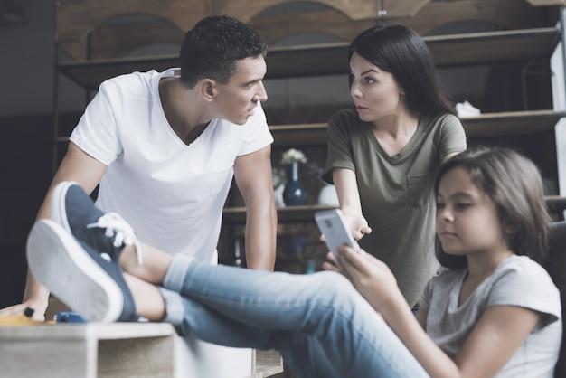 Garota usa smartphone e ignora os pais repreendendo Foto Premium
