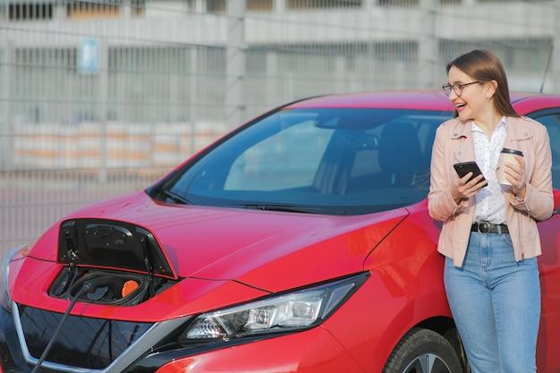 Garota use café enquanto estiver usando o smartphone e aguardando a fonte de alimentação conecte-se a veículos elétricos para carregar a bateria no carro Foto Premium