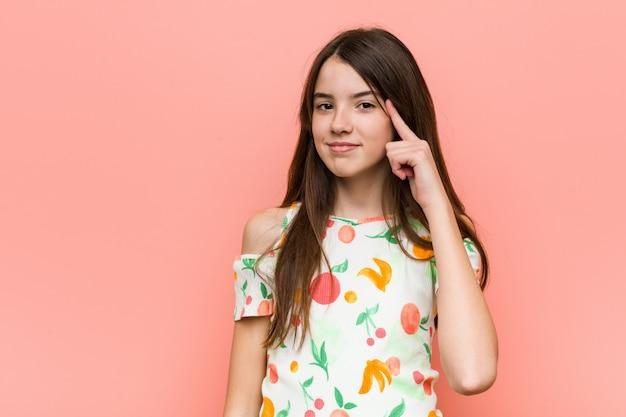 Garota vestindo roupas de verão contra uma parede rosa, apontando a cabeça com um dedo Foto Premium
