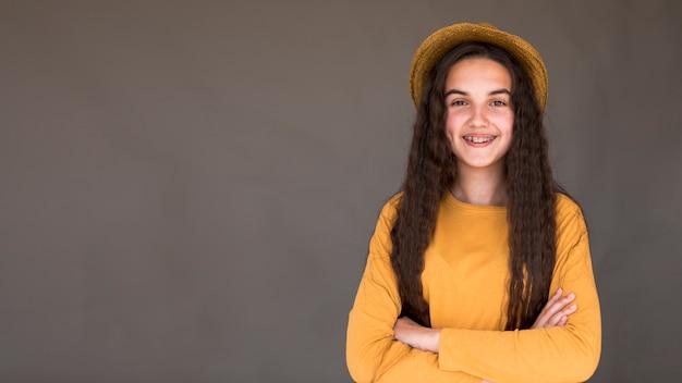 Garota vestindo um chapéu de palha posando com espaço de cópia Foto gratuita