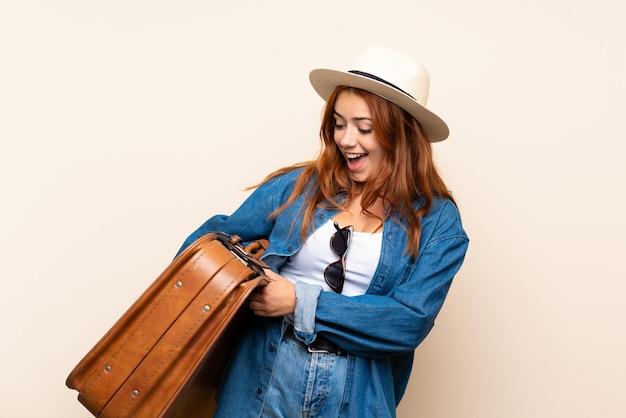 Garota viajante ruiva com mala com expressão feliz Foto Premium