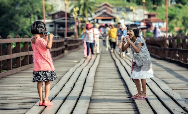 Garotas asiáticas falando em um telefone de lata Foto Premium