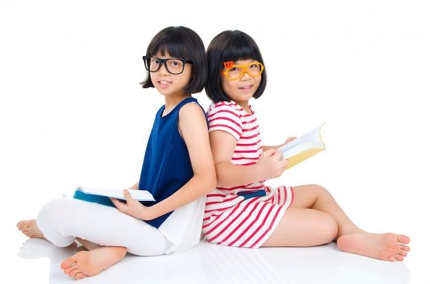Garotas asiáticas vestindo óculos sentado no chão com livros Foto Premium