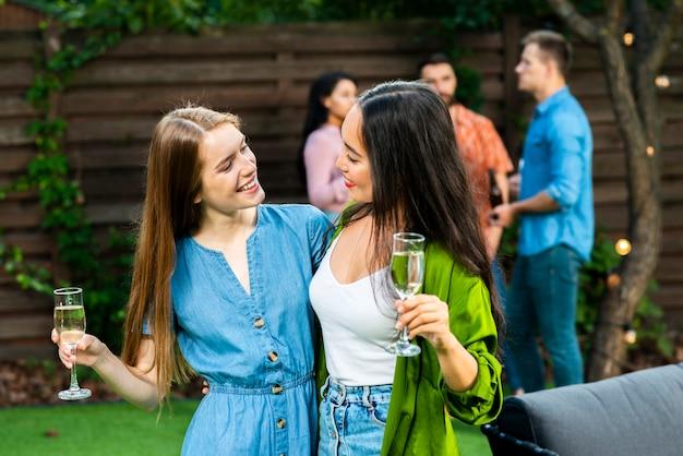 Garotas bonitas com bebidas olhando uns aos outros Foto gratuita