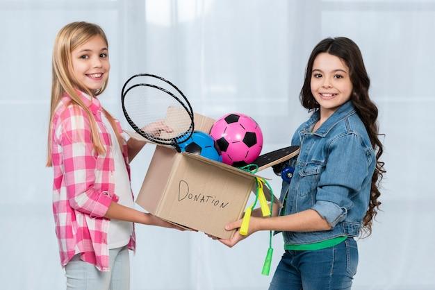Garotas bonitas com caixa de doação Foto gratuita