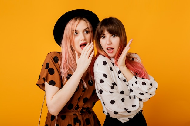 Garotas bonitas com rosto emocional posando sobre parede amarela Foto gratuita