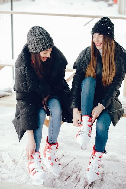 Garotas bonitas e bonitas com um suéter branco em uma cidade de inverno Foto gratuita