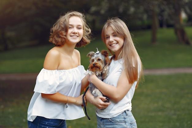 Garotas bonitas em um parque brincando com cachorro Foto gratuita