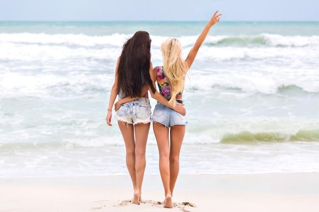 Garotas bronzeadas com pernas longas em pé perto do oceano e apreciando a vista incrível da natureza retrato de corpo inteiro ao ar livre de senhoras descalças em shorts jeans, passando a manhã no mar. Foto gratuita