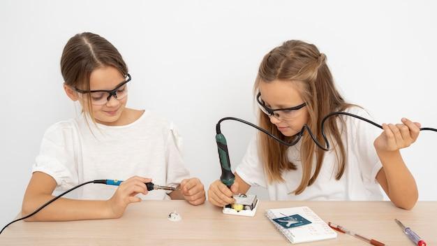 Garotas com óculos de proteção fazendo experimentos científicos juntas Foto gratuita