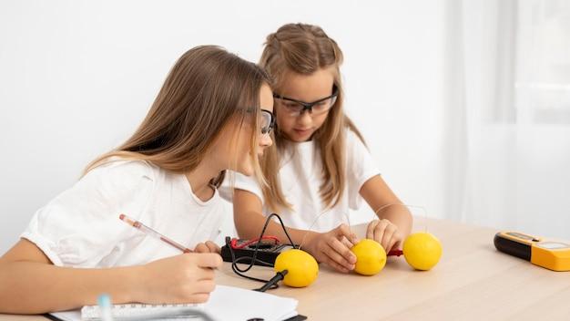 Garotas fazendo experimentos científicos com limões Foto gratuita