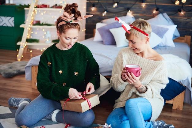 Garotas felizes preparando um presente de natal Foto gratuita