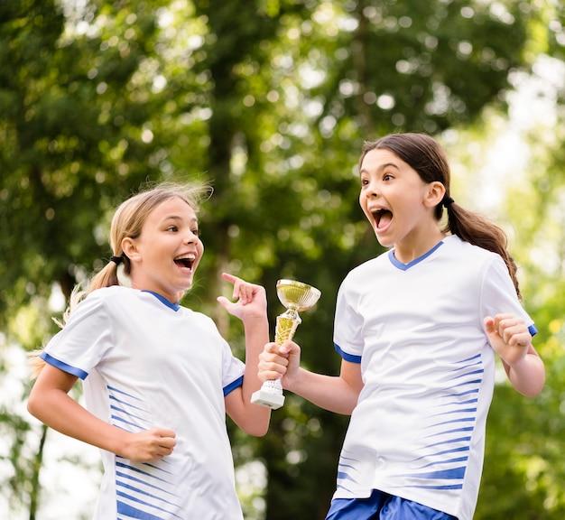 Garotas ganhando um troféu depois de vencer uma partida de futebol Foto gratuita