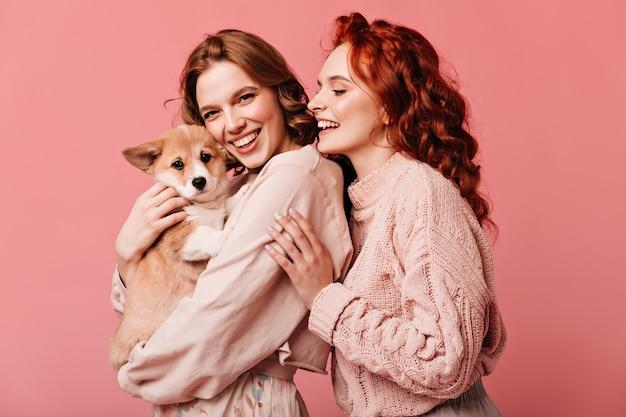 Garotas maravilhosas segurando cachorro bonito isolado no fundo rosa. foto de estúdio de sorridentes senhoras europeias posando com animal de estimação. Foto gratuita
