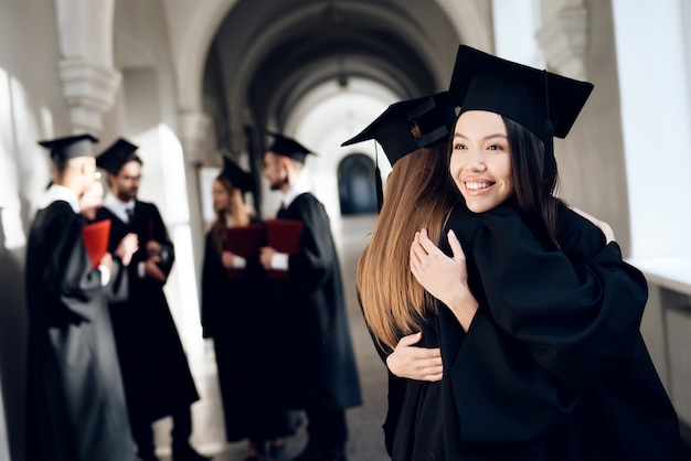 Garotas se abraçam no corredor da universidade em suas vestes. Foto Premium