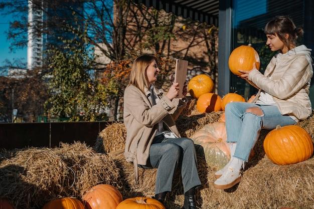 Garotas se divertem entre abóboras e palheiros em uma rua da cidade Foto gratuita