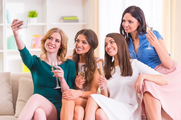 Garotas tiram selfies e bebem champanhe em casa. Foto Premium