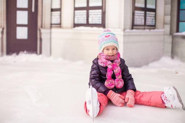 Garotinha adorável sentado no gelo após a queda Foto Premium