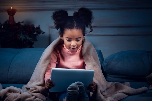 Garotinha afro-americana feliz durante a videochamada com laptop e dispositivos domésticos, parece encantada Foto gratuita