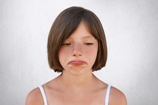 Garotinha chateada, com pele sardenta e cabelos cortados, curvando os lábios com uma expressão triste, infeliz ao descobrir que os pais não compraram seu brinquedo. menina bonita sardenta vai chorar Foto gratuita