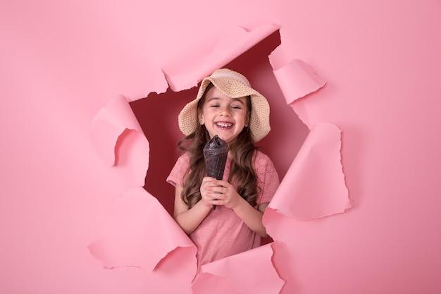 Garotinha engraçada espiando pelo buraco com um chapéu de praia e sorvete nas mãos, sobre um fundo rosa colorido, espaço para texto, tiro em estúdio Foto gratuita