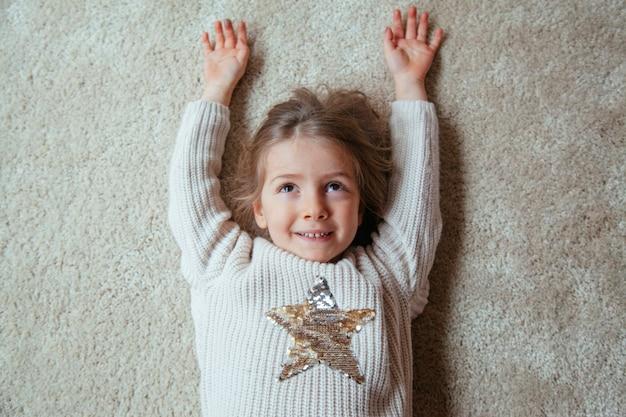 Garotinha loira sorrindo com uma estrela na camisola dela Foto Premium