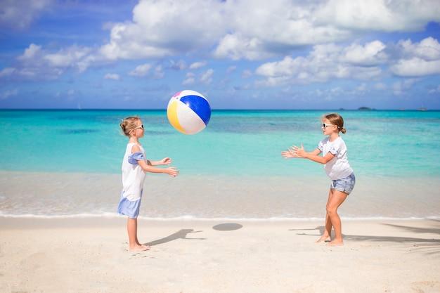 Garotinhas adoráveis brincando com bola na praia Foto Premium