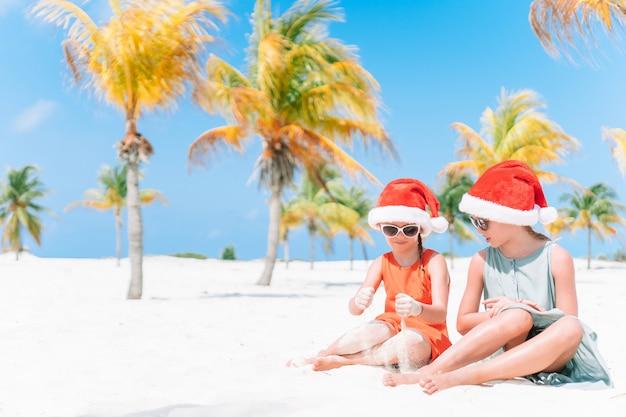 Garotinhas adoráveis em chapéus de papai noel durante as férias de praia se divertir juntos Foto Premium