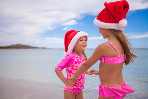 Garotinhas adoráveis em chapéus de papai noel durante as férias de praia Foto Premium