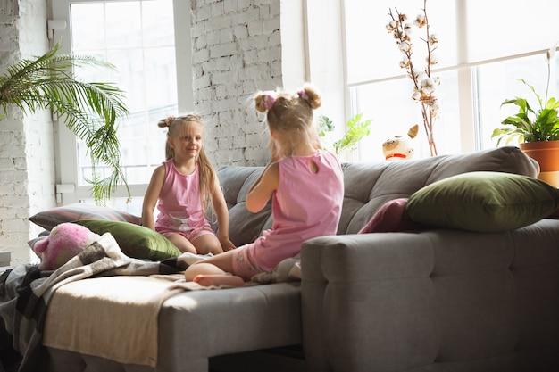 Garotinhas calmas acordando em um quarto de pijama fofo, estilo caseiro e conforto Foto gratuita