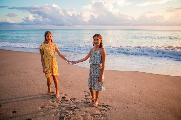 Garotinhas engraçadas e felizes se divertem muito na praia tropical brincando juntas Foto Premium