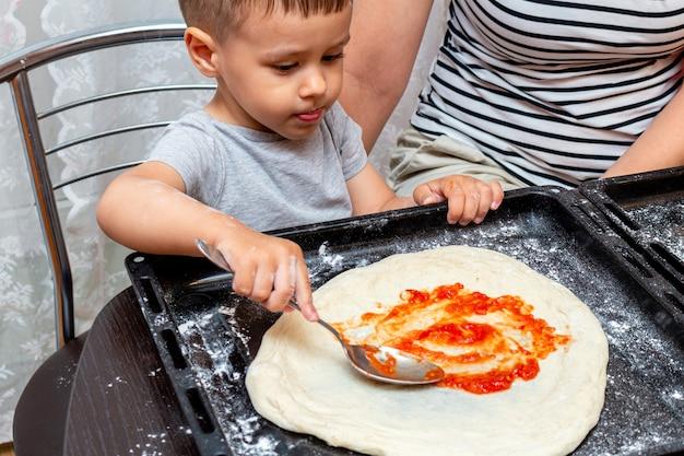 Garotinho, ajudando a mãe a fazer pizza em casa Foto Premium